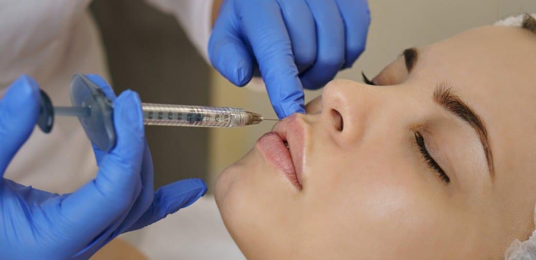 chirurgien pratiquant une injection d'acide hyaluronique sur le visage d'une jeune femme